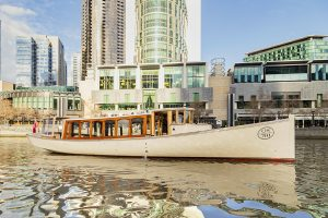 Crown Casino forms an impressive background behind the luxuriously appointed MV Birrarung- a melbourne hire boat